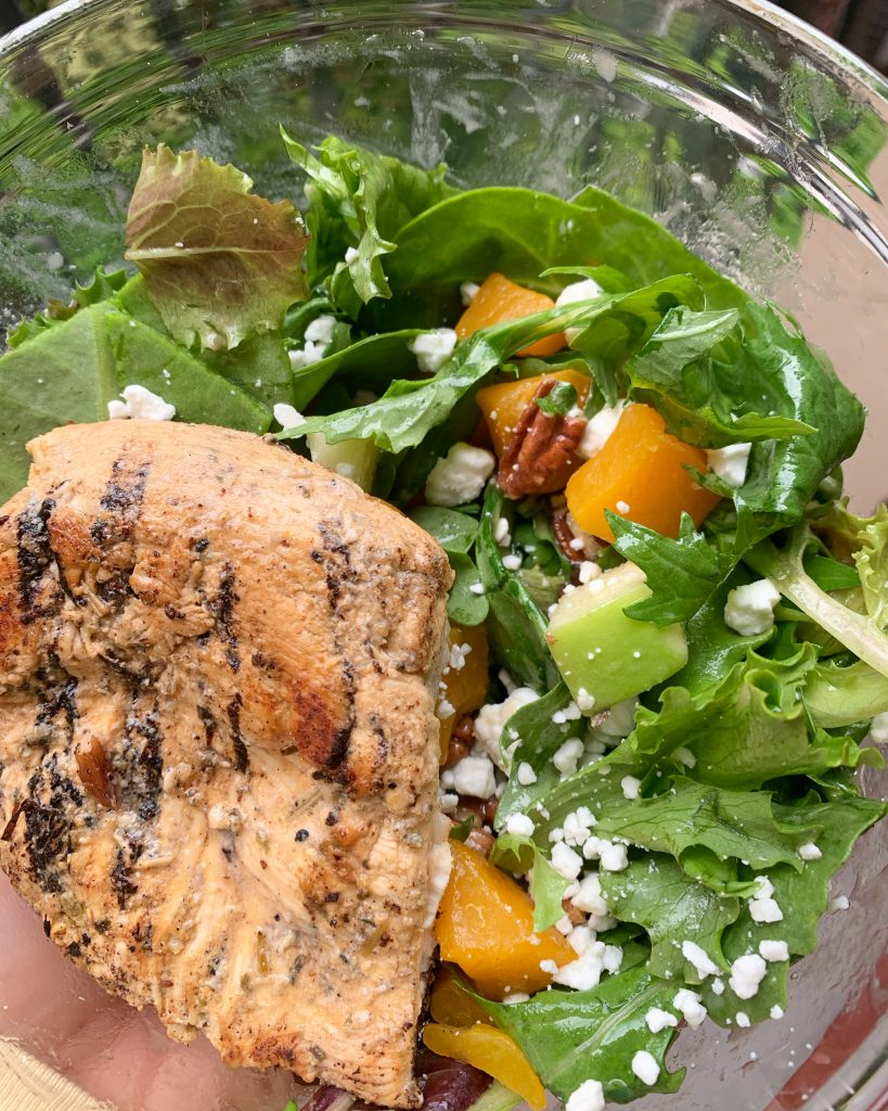 Grilled chicken on a bed of greens with goat cheese, diced apple, pecans, and butternut squash.